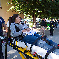 Paulina Houston, playing a gunshot victim in the active shooter drill at the library being transported by Gallup Fire Department, Thursday morning.