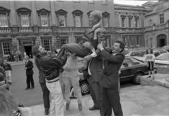 Dail Resumes After General Election.  (T3)..1989..29.06.1989..06.29.1989..29th June 1989..After the general election  members of the 26th Dáil arrived in Leinster House, Dublin to take their seats in the parliamentary chamber...A newly elected TD is tosed in the air by his supporters as he arrives to take his seat in Dáil Éireann