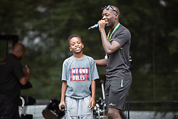 © Licensed to London News Pictures . 12/08/2018. Manchester , UK . Young musician POSITIVE PLATINUM performs on stage . The second day of the annual Caribbean Carnival in Alexandra Park in Moss Side , celebrating music , food and Afro-Caribbean culture . A nearby shooting overnight lead to at least ten people injured . Ten people are in hospital . Photo credit : Joel Goodman/LNP