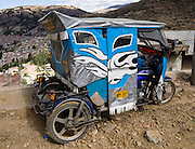 A mototaxi (three-wheeled auto rickshaw) provides cheap public transportation in Huaraz, in the Andes Mountains, Ancash Region, Peru, South America.