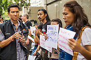 25 JANUARY 2013 - BANGKOK, THAILAND: A man wearing a Thai police vest takes notes and photographs free speech protesters in front of the Criminal Court building in Bangkok. About 70 people protested on behalf of freedom of speech and expression at the Criminal Court building in Bangkok Friday. The protest was called as a result of the 10 year sentence handed down against magazine editor Somyot Prueksakasemsuk on Lese Majeste charges earlier in the week. The protesters burned several legal documents to demonstrate they said was their loss of free speech during the protest.     PHOTO BY JACK KURTZ