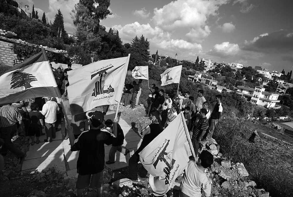 Friends and relatives gather to bury the body of Sayeed Adel Akkash, a likely Hezbollah official, in the village of Dweir near Nabatiyeh, southern Lebanon on July 13, 2006. Israeli forces targeted Sayeed Akkash's house in the middle of the night, killing Sayeed, his wife and their ten children. Israeli forces intensified their attacks in Lebanon, with airstrikes that blasted the country's only international airport and the Hezbollah TV station in what was Israel's heaviest air campaign against Lebanon for 24 years.