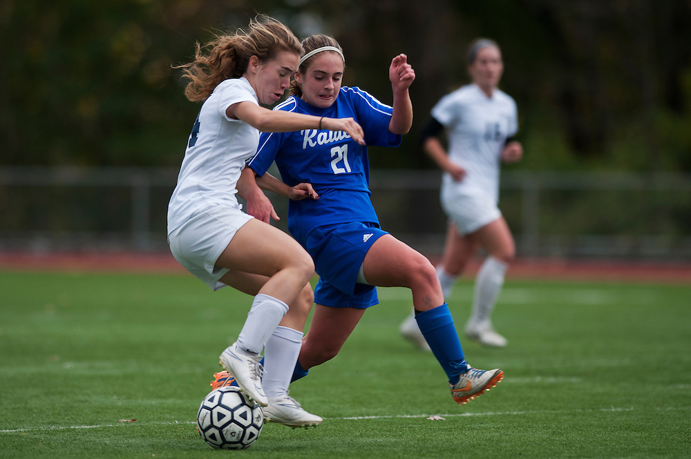 Burlington's Micahla Combes (4) and U-32's Maggie Kirby (21) battle for the ball during the girls playoff soccer game between the U-32 Raiders and the Burlington Sea Horses at Buck Hard Field on Friday afternoon October 24, 2014 in Burlington, Vermont (BRIAN JENKINS, for the Free Press)
