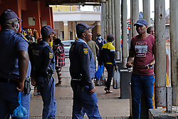 JOHANNESBURG, SOUTH AFRICA - APRIL 18: SAPS officers during a South African Police Service (SAPS) Metro Police and Army supported patrol in Rockey Street, Yeoville. Random searchs and social distancing measures on April 18, 2020 in Johannesburg South Africa. Under pressure from a global pandemic. President Ramaphosa declared a 21 day national lockdown extended by another two weeks, mobilising goverment structures accross the nation to combat the rapidly spreading COVID-19 virus - the lockdown requires businesses to close and the public to stay at home during this period, unless part of approved essential services. (Photo by Dino Lloyd)