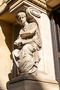 Victorian sculpture of woman reading a book outside old library building in city centre, Cardiff, South Wales, UK