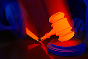A glowing gavel breaks in two as it strikes a block on a judge's bench.Black light