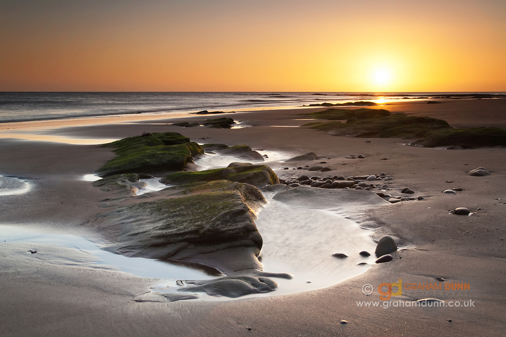 Sunrise over the sands and rock formations of Hauxley Haven, Northumberland coast, England, UK.