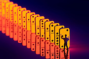 A man stands standing next to a gigantic line of dominoes reaches out to push the first one.Black light