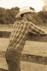 profile of a cowboy leaning on a fence