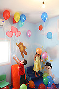 Young girl and boy play with balloons in a kindergarten playroom