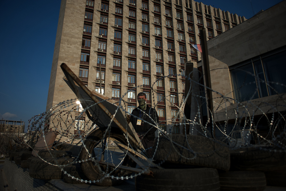 A pro-Russia activist takes guard behind a newly build barricade set up by pro-Russia activists around the Donbass Regional Government building in central Donetsk. The Ukrainian government in Kiev gave a 48 hour deadline for the activists to abandon the building.