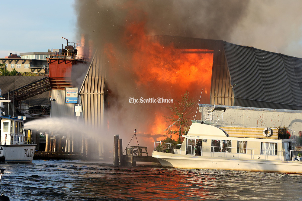 A boat house, just East of Covich Williams fuel dock at Canal Cove Marina in Seattle, was engulfed in flames. (Greg Gilbert/The Seattle Times)