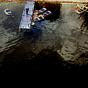 a dock at Bekonscot model village with policeman standing on it and boats.