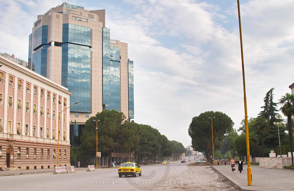 The modern Sky tower office complex On the boulevard Bulevardi Deshmoret e Kombit. Yellow Taxis on the wide street. Tirana capital. Albania, Balkan, Europe.