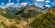 A tramper descends Gillespie Valley from Gillespie Pass under Mount Awful (2192 m / 7190 ft) in the Southern Alps, on Gillespie Pass Circuit in Mount Aspiring National Park, Otago region, South Island of New Zealand. UNESCO lists Mount Aspiring as part of Wahipounamu - South West New Zealand World Heritage Area. This image was stitched from multiple overlapping photos.