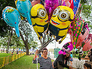 10 JANUARY 2015 - BANGKOK, THAILAND:  A balloon vendor waits for customers during Children's Day celebrations at a Royal Thai Army base in Bangkok. National Children's Day falls on the second Saturday of the year. Thai government agencies sponsor child friendly events and the military usually opens army bases to children, who come to play on tanks and artillery pieces. This year Thai Prime Minister General Prayuth Chan-ocha, hosted several events at Government House, the Prime Minister's office.   PHOTO BY JACK KURTZ