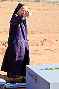 "18 MARCH 2010 - SURPRISE, AZ: Sister Mary Ruth Dittman (CQ) sprinkles holy water on a casket in White Tanks Cemetery on Camelback Rd. in an unincorporated part of the county near Surprise. The county spent about $2.5 million to inter indigent people in what is Maricopa County's ""potters field."" About 3,000 people, children and adults, are buried in the dusty field west of Phoenix.       PHOTO BY JACK KURTZ"