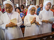 18 SEPTEMBER 2016 - BANGKOK, THAILAND:   Catholic nuns pray during the 100th anniversary mass for the sanctuary of Santa Cruz Church. Santa Cruz Church was establised in 1769 to serve Portuguese soldiers in the employ of King Taksin, who reestablished the Siamese (Thai) empire after the Burmese sacked the ancient Siamese capital of Ayutthaya. The church was one of the first Catholic churches in Bangkok and is one of the most historic Catholic churches in Thailand. The first sanctuary was a simple wood and thatch structure and burned down in the 1800s. The church is in its third sanctuary and was designed in a Renaissance / Neo-Classical style. It was consecrated in September, 1916. The church, located on the Chao Phraya River, serves as a landmark for central Bangkok.     PHOTO BY JACK KURTZ