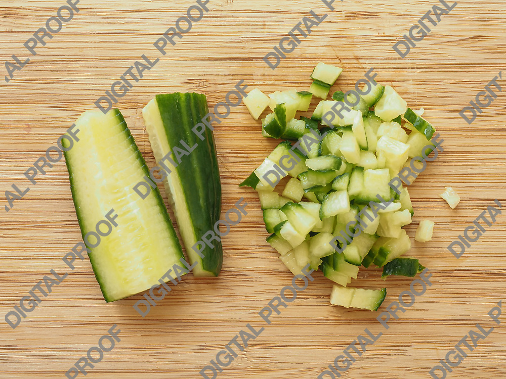 Cucumber cutted in half and in dices over a wood table viewed from above - flaylat concept