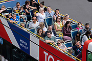 Seen from the elevation from the Marble Arch Mound, tourists listen to the commentary in many languages, on the top open-air deck of a tour bus in central London, on 11th August 2021, in London, England.