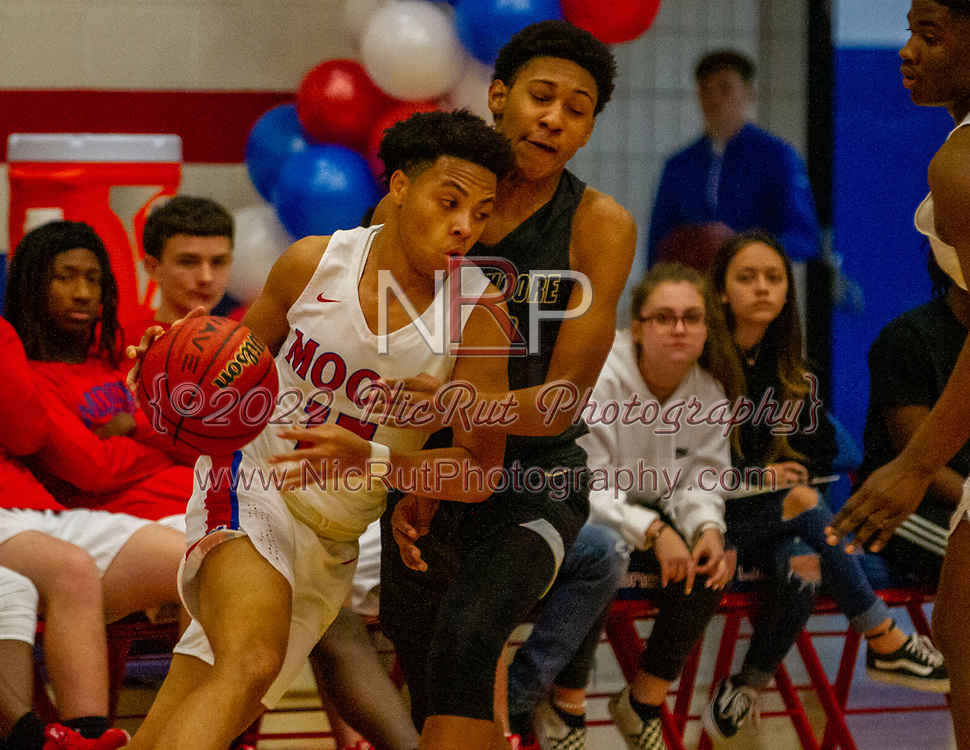 Moore's Justin Martin drives the basket as Southmoore's Domingo Ward stay toe to toe with him during their game on Tuesday, December 18, 2018 at Moore High School.