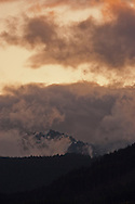 Forested ridges in the Olympic National Forest lie below an evening sky with  alpenglow colored clouds, Olympic Peninsula, Washington, USA