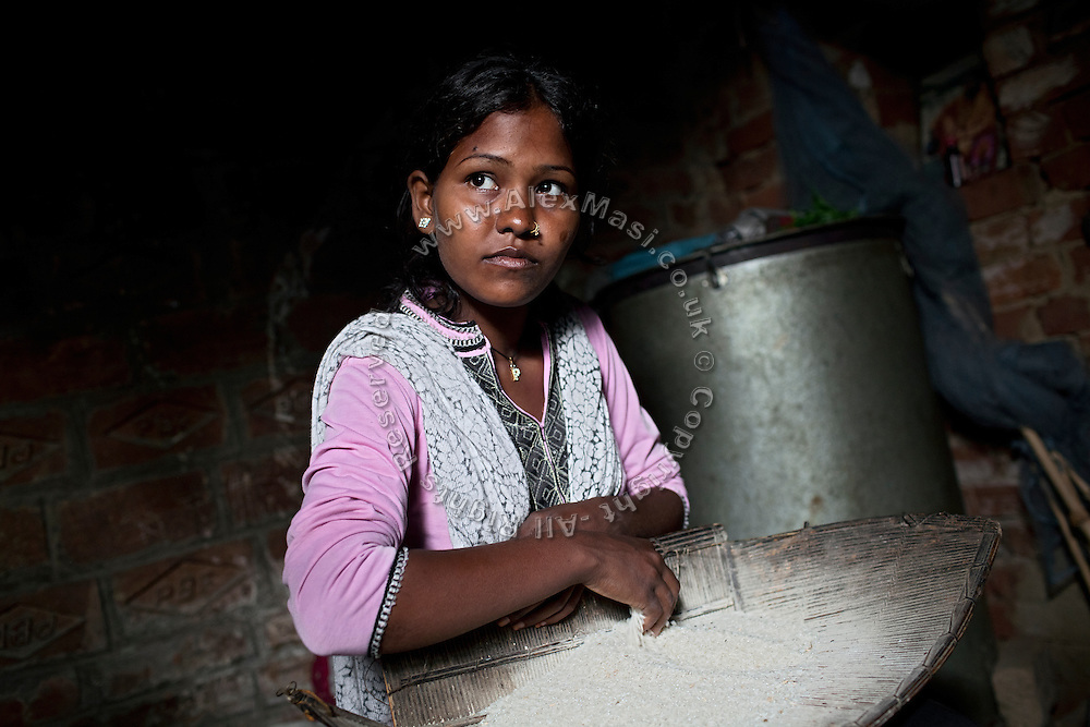 (name changed) Neelam Bharadwaj, 16, is preparing some rice for cooking while sitting inside her family's home in Rajbhar village, located around 20 kilometres away from Varanasi, in Uttar Pradesh, India. Neelam was raped when she was 13 years old. After walking to a local shop on the main road neighbouring her village, she was forcibly picked up by two men. While one of them was raping her in the bushes, the other watched out. After some time, she managed to free herself and run away, hiding under a bridge in cold dirty water for several hours. When she returned home in the morning, the family was too afraid to go to the police, but activist Mangla Parsad, 34, from PVCHR, convinced the family to take the right action. The police initially insulted and threatened the family for bringing the facts up, but filed the official case (FIR) nevertheless. The rape was not mentioned in the file due to an inaccurate and superficial medical record that did not, in fact, mention it. Because of social shame facing by victims of rape in India, the family agreed to wed Neelam to an older man, with help of an agent. After the marriage, her husband raped her again for a whole month before she decided to return home with her family. Neelam's father works in the metal industry in Mumbai and manages to send around 2-3000 INR every month. He only visits the family once in a year. Neelam goes to school and she is studying in 11th Class Standard. She is interested in doing BA in Arts after completing her high school 12th final year.