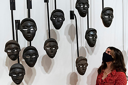 """© Licensed to London News Pictures. 27/09/2021. LONDON, UK. A staff member views """"Chorus"""", 2016, by Theaster Gates. Preview of """"A Clay Sermon"""", a new exhibition by Chicago artist Theaster Gates.  The display, an investigation into the significance of clay in global trade, colonial expansion, slavery and abolitionism in the UK, is on show at Whitechapel Gallery 29 September to 9 January 2022.  Photo credit: Stephen Chung/LNP"""