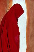 A woman in a red veil walks beside a colorful earthen wall  in Rajasthan, India.