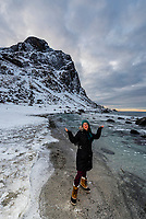 Young woman enjoying the winter landscape at Uttakleiv Beach, Vestavagoya Island, Lofoten Islands, Arctic, Northern Norway.
