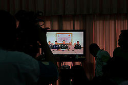 © Licensed to London News Pictures. 22/05/2014. A Camera man video tapes the military leaders addresses the nation on tv announcing a coup during a meeting hosted by Thailand's army chief at the Army Club, between representatives from both sides of the country's political groups the PDRC & UDD at the conclusion of the meeting the Thailand army imposed a Military Coup, in Bangkok Thailand.  Photo credit : Asanka Brendon Ratnayake/LNP