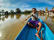 30 SEPTEMBER 2016 - SAI NOI, AYUTTHAYA, THAILAND:  A man paddles his boat through the flooded Wat Boonkannawas in Sai Noi. The Chao Phraya River, the largest river that runs through central Thailand, has hit flood stage in several areas in Ayutthaya and Ang Thong provinces. Villages along the river are flooded and farms are losing their crops due to the flood. This is the same area that was devastated by floods in 2011, but the floods this year are not expected to be as severe. The floods are being fed by water released from upstream dams. The water is being released to make room for heavy rains expected in October.     PHOTO BY JACK KURTZ