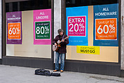 A busker singing outside the Folkestone Debenhams store in the final few days of the 'Everything Must Go' sale before closing down in Folkestone, Kent. United Kingdom. The company announced the closure of 19 stores across the UK after going into administration in 2019.  (photo by Andrew Aitchison / In pictures via Getty Images)