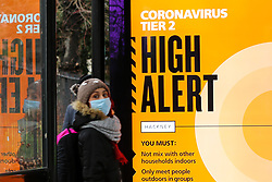 © Licensed to London News Pictures. 11/12/2020. London, UK. A woman wearing a face covering near a 'Coronavirus Tier Two - High Alert' COIVD-19 public information campaign digital poster at a bus stop in north London amid fears of London going into tougher lockdown restrictions as early as next week. According to Public Health England, 22 of the London's 32 boroughs have infections rates higher than the national seven-day average of 150 per 100,000 people. Photo credit: Dinendra Haria/LNP