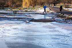 © Licensed to London News Pictures. 10/02/2021. London, UK. A runner runs past a frozen cycle path in Richmond Park, South West London this morning. The Met Office have issued weather warnings for extreme cold with temperatures forecast to drop to as low as -10c in London tonight as Storm Darcy continues to bring travel chaos to the South East and the rest of the UK.  Photo credit: Alex Lentati/LNP