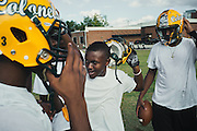 """BIRMINGHAM, AL – SEPTEMBER 10, 2015: Quintarius Monroe (center) enters a huddle during football practice. A type 1 diabetic, Monroe requires frequent blood sugar testing and supervision when self-administering insulin. When care from qualified personnel at his school in Center Point became unavailable, Monroe was forced to transfer several miles away from his locally zoned school to attend Woodlawn High School. The Americans with Disabilities Act requires schools to provide """"reasonable accommodation"""" for students with medical conditions, but given that most schools no longer retain school nurses, many schools are failing to provide adequate care for their students.<br /> CREDIT: Bob Miller for The New York Times"""