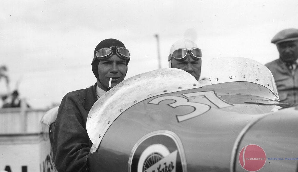 Driver Zeke Meyer (white helmet) and riding mechanic Walter Mitchell (black helmet) pose in the #37 Studebaker Special at the 1932 Indianapolis 500.