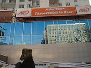 Bank Gebaeude im Zentrum der jakutischen Haupstadt Jakutsk. Jakutsk hat 236.000 Einwohner (2005) und ist Hauptstadt der Teilrepublik Sacha (auch Jakutien genannt) im Föderationskreis Russisch-Fernost und liegt am Fluss Lena. Jakutsk ist im Winter eine der kaeltesten Großstaedte weltweit mit durchschnittlichen Winter Temperaturen von -40.9 Grad Celsius. Die Stadt ist nicht weit entfernt von Oimjakon, dem Kaeltepol der bewohnten Gebiete der Erde.<br /> <br /> Man passing a bank in the city centre of Yakutsk. Yakutsk is a city in the Russian Far East, located about 4 degrees (450 km) below the Arctic Circle. It is the capital of the Sakha (Yakutia) Republic (formerly the Yakut Autonomous Soviet Socialist Republic), Russia and a major port on the Lena River. Yakutsk is one of the coldest cities on earth, with winter temperatures averaging -40.9 degrees Celsius.