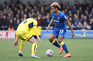 AFC Wimbledon striker Lyle Taylor (33) taking on Oxford United midfielder Josh Ruffels (14) during the EFL Sky Bet League 1 match between AFC Wimbledon and Oxford United at the Cherry Red Records Stadium, Kingston, England on 10 March 2018. Picture by Matthew Redman.