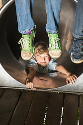 Boy sliding in a tunnel slide with two children dangling their feet, Munich, Bavaria, Germany