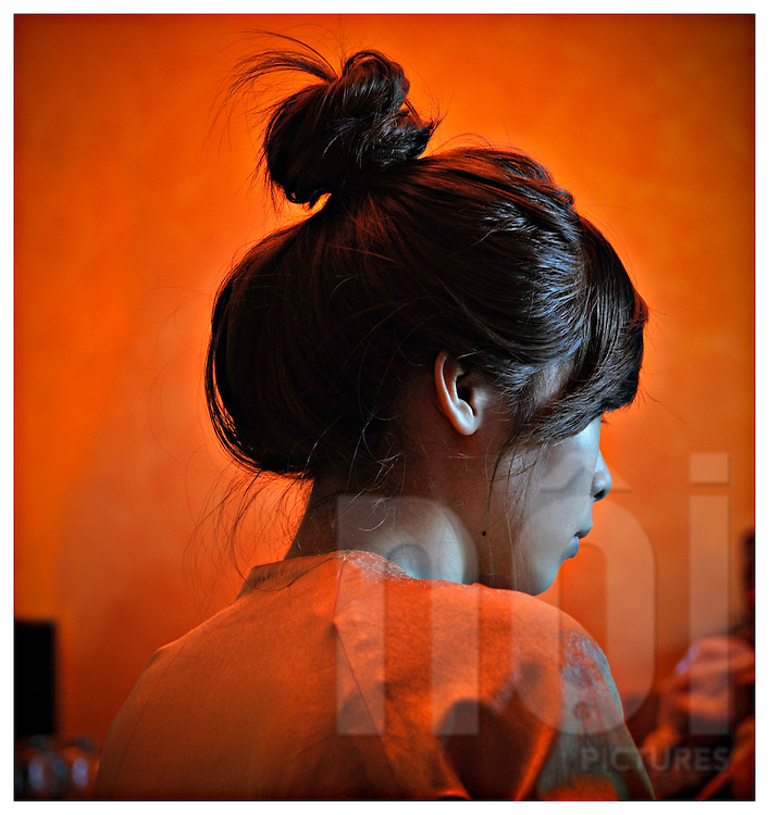 A young Vietnamese woman wearing her hair in a high bun sits with her back to the camera in an orange room. Nha Trang, Vietnam, Southeast Asia