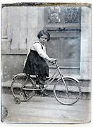 girl sitting on a bicycle with extra wheel support France circa 1920s