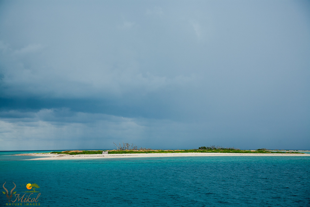 Blue and grey clouds approachinga small,  barren, closed, subtropical island in the Dry Tortugas. Blue and aqua water
