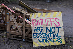 Wendover, UK. 9th April, 2021. A sign reads 'Bailiffs Are Not Essential Workers' outside Wendover Active Resistance Camp, which is occupied by activists opposed to the HS2 high-speed rail link. Tree felling work for the project is now taking place at several locations between Great Missenden and Wendover in the Chilterns AONB, including at Jones Hill Wood.