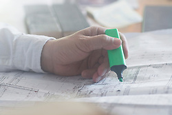 Cropped image of a businessman with highlighter working on blueprint in the office, Freiburg im Breisgau, Baden-Wuerttemberg, Germany