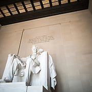 Lincoln Memorial Statue Front Left View. The statue of a seated President Abraham Lincoln that is the centerpiece of the Lincoln Memorial in Washington DC. It is 19 feet high and carved in Georgia white marble. A seated Lincoln looks out towards the Reflecting Pool, Washington Monument, and towards the US Capitol Building at the other end of the National Mall.