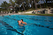 Couple playing in the pool of a country holiday house, 25th August 2014, Lagrasse France.