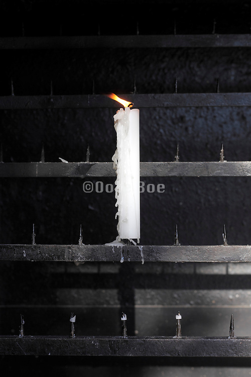 burning offering candle with wind blowing on the flame