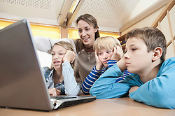 Female childcare assistant and three boring children looking at laptop