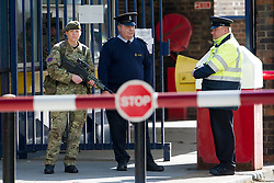 © London News Pictures. 23/05/2013. Woolwich, UK. A female soldier and security on guard outside   Woolwich Military Barracks in Woolwich, London where a member of the armed forces was attacked yesterday (22/05/2013) by two men in what is being described as a terrorist attack. Photo credit: Ben Cawthra